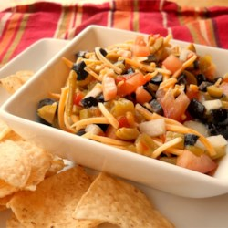 Olive Dip Recipe - This colorful party dip, full of shredded Cheddar cheese, tomatoes, and olives, is great served with chips for your next gathering.