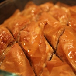 Easy Baklava Recipe and Video - Phyllo dough is layered with butter, cinnamon and nuts and baked, then topped with a honey syrup and allowed to cool before eating.
