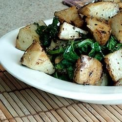 Roasted Potatoes with Greens Recipe - Roasted potatoes mingle with fresh spinach in a sauce of garlic, butter, sea salt and fresh rosemary. Finish with a drizzle of olive oil and/or a good shredded hard cheese like Parmesan or Pecorino if you like.