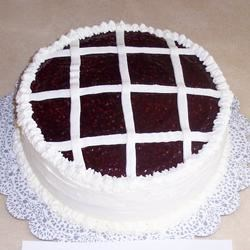 Raspberry Walnut Torte Recipe - A dense cake dotted with ground walnuts. The layers are stacked alternately with jam and a fluffy cream cheese icing and topped off with an elegant design.
