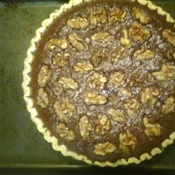 Walnut Brownie Pie Recipe -  This pie is like a thick, fudgy brownie studded with bits of walnuts. Sweetened condensed milk, butter and cocoa are heated gently on the stove and then combined with eggs, flour, vanilla and walnuts. This luscious filling is spooned into a prepared pie pan, baked, and served warm with fudge sauce and whipped cream.