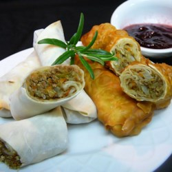 Leftover Turkey Spring Rolls with Cranberry Sweet and Sour Dipping Sauce Recipe - Cooked turkey meat gets an Asia-meets-Thanksgiving flavor when you roll it into prepared spring roll wrappers with stir-fried cabbage and garlic, then bake until crisp and serve with a cranberry-flavored dipping sauce.