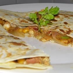 Mango Quesadillas Recipe - The flavor and texture of mango goes well with black beans and Cheddar cheese in this easy main dish. The recipe uses vegetarian chicken substitute, but real chicken would work just as well.