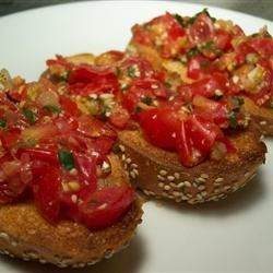 Jen's Tomato Arugula Bruschetta Recipe - This is a wonderful combination of ripe plum tomatoes, Parmesan cheese, fresh garlic and arugula that together pack a punch when served on a slice of French bread.