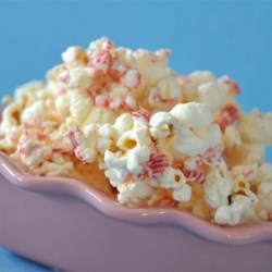 Candy Cane Popcorn Recipe - Popcorn mixed with white candy coating and crushed peppermint candy canes makes a quick, simple treat that's a little different for the cookie tray. Package it up in a pretty cellophane bag for a sweet gift. This recipe uses an air popper to make popcorn without added oil.