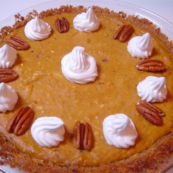 Pumpkin Cheesecake Pie Recipe -  Both the crust and the filling are super in this delicious pie. The crust is a tasty crumble of graham cracker, pecan and ginger. This lovely mixture is pressed into a 9-inch pie tin, and filled with a scrumptious pumpkin pie filling boasting cream cheese, brown sugar, cream, eggs, cinnamon, ginger, nutmeg and cloves. The pie is then baked and garnished with whipped cream and pecan halves.