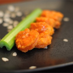 Buffalo Shrimp Recipe - Succulent shrimp twice-coated in seasoned flour and deep fried, then coated in an extremely spicy butter sauce. Perfect for those who crave the heat. For added heat, slice up some fresh cayenne or jalapeno peppers to sprinkle over the top. Serve with lemon wedges and blue cheese dressing on the side.