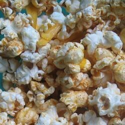 Popcorn Nachos Recipe - Mexican-style spices and shredded Cheddar cheese are lively additions to plain popcorn.