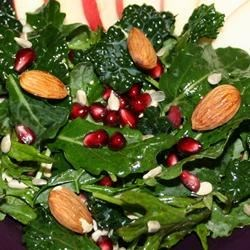 Kale Salad with Pomegranate, Sunflower Seeds and Sliced Almonds Recipe - This zesty combination of raw pomegranate and tender fresh kale makes a surprisingly great salad! The addition of almonds and sunflower seeds gives a tasty crunch.