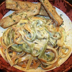 Easy Fettucine Alfredo Recipe - Fresh and dried basil add a distinctive flair to this simple, creamy dish. Parmesan cheese, evaporated milk, dried basil, lemon juice and pepper are cooked with the boiled and drained noodles, with fresh basil and more Parmesan sprinkled over the top.