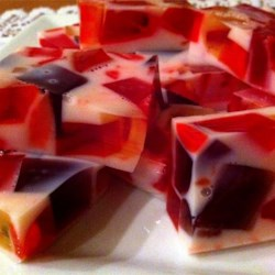 Broken Window Glass Recipe - Cubes of lime, orange, and cherry Jell-O® float in a base of whipped topping, lemon gelatin, and pineapple juice in this colorful dessert.