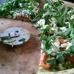 Goat Cheese Arugula Pizza - No Red Sauce! Recipe - This pesto-based pizza is an amazingly simple and delicious variation to your regular pizza. Adapted from a pizza idea at a popular Neapolitan pizza restaurant in Washington DC, it'll take minutes to make and will disappear in even less time!