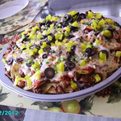 Italian Nachos Restaurant-Style Recipe - Italian sausage, pepperoni, banana peppers, mozzarella, and pizza sauce make for great nachos.