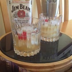 Classic Whiskey Sour Recipe - Whiskey, lemon juice and simple syrup are served ice cold garnished with a maraschino cherry. If it's not made from scratch, it ain't a Whiskey Sour.
