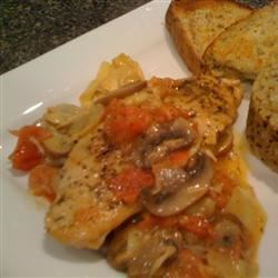 Easy Tuscan Chicken Recipe - A zingy white white sauce with mushrooms, artichoke hearts, and tomatoes is served over peppery chicken breasts in this simple weeknight dish.
