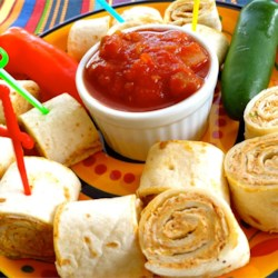 Tortilla Rollups  Recipe - Cream cheese, sour cream, and taco seasoning are stirred up and spread on soft flour tortillas in this easy snack.