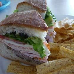 Joanne's Super Hero Sandwich Recipe - Much like the N'awlins muffuletta, this is a large sandwich layered in a round loaf of crusty bread. You can be flexible and vary the cold cuts that you use according to personal preference! Must be done a day ahead, which makes for an easy serve.