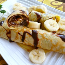 State Fair Crepes Recipe - Thin and elegant crepes are spread with peanut butter and hazelnut spread and wrapped around bacon and fried bananas for a savory-sweet, fancy brunch dish or dessert that will wow your family and guests.