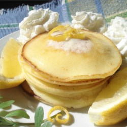 Romantic Lemon Cheesecake Pancakes Recipe - Light and delicate pancakes made with cream cheese, egg, and just a bit of flour and sugar are sprinkled with confectioners' sugar and drizzled with lemon juice for a romantic brunch item.