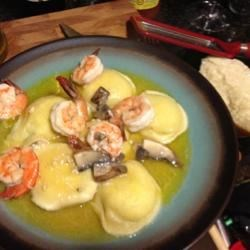 Portobello Mushroom Ravioli with Prawns Recipe - Overwhelm your dinner guests with ravioli blanketed by a lavishly rich sauce of sliced Portobello mushrooms sauteed with garlic and simmered with white wine, butter, capers, lemon juice and prawns.