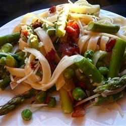 Creamy Asparagus and Peas Pasta Recipe - Fresh fettuccine pasta is combined with asparagus, crisp bacon, and green peas for a light and fresh main dish.
