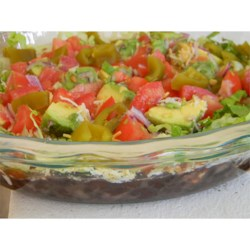 Manda's Seven Layer Taco Dip Recipe - A classic and fresh layered dip has refried black beans, fresh tomatoes and avocados, and salsa, all topped with cheese, lettuce, and pickled jalapenos. Bring lots of chips!