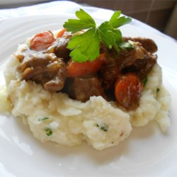 Beer Braised Irish Stew and Colcannon Recipe - This beef stew, richly flavored with dark beer, slowly cooks down until tender with carrots and onions. It's served on buttery cabbage mashed potatoes.