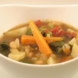 Italian Vegetable Soup with Beans, Spinach & Pesto Recipe - Cannellini beans and a plethora of vegetables - bell peppers, carrots, celery, potatoes, peas, and spinach - make this healthy soup hearty and satisfying.