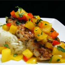 Mahi Mahi with Coconut Rice and Mango Salsa Recipe - Mahi mahi is broiled to perfection and served on a bed of fragrant jasmine rice with a warm mango sauce.