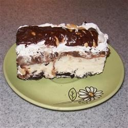 Mmm-Mmm Ice Cream Cake Recipe - A nutty cereal crust full of almonds and coconut forms the base of a vanilla ice cream dessert topped with a homemade chocolate syrup and served frozen.
