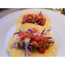 Quick and Easy Fish Tacos Recipe - Soft, warm corn tortillas are filled with crisp fish sticks and cabbage, and topped with tartar sauce and salsa.