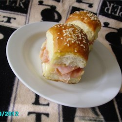 Jen's Mini Ham and Cheese Rolls Recipe - These toasted little ham and cheese rolls are perfect appetizers for parties. They are brushed with a butter and honey mustard glaze for a savory sweet flavor.