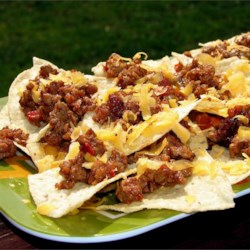 Jen's Nachos Recipe - Barbecue sauce is the surprise ingredient here--it's sauteed with ground beef and more traditional nacho toppings for a tangy twist on this everyday dish.