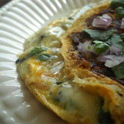 Blue Mushroom Omelet Recipe - Eggs cooked with red onion, cremini mushroom, and baby spinach are folded over a layer of melted Stilton and mozzarella cheeses in this omelet recipe.