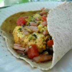 Egg Pesto Breakfast Wrap Recipe - Pesto and cheese-flavored scrambled eggs, brightened with cherry tomato slices and marinated artichoke hearts, are wrapped up in a flour tortilla with a slice of turkey bacon for a light, savory wrap that's perfect for breakfast or lunch.