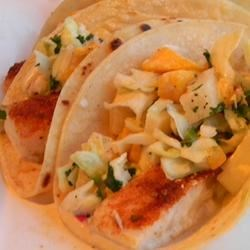 Easy Fish Tacos with Mango-Pineapple Slaw Recipe - Warm-weather fruits like mango and pineapple add a tropical flavor to a simple slaw that tops this baked cod taco.