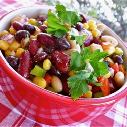 Mexican Bean Salad Recipe - Black beans, kidney beans, and cannellini beans combine with corn, bell pepper, and red onion in this easy and colorful salad. It's tossed with a sensational dressing made with fresh lime juice, cilantro, and cumin.
