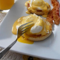 Eggs Benedict Recipe - Hot buttered English muffins, Canadian-style bacon, and poached eggs are topped with a heavenly drizzle of hollandaise sauce. The best brunch in the world!