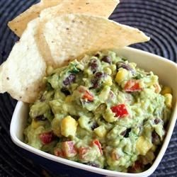 Corn and Black Bean Guacamole Recipe - This chunky guacamole has red pepper, corn, red onion, and black beans for a colorful dip for tortilla chips.