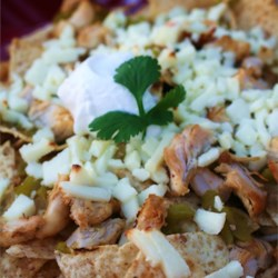 Chicken Nachos Recipe - Super-simple but totally killer nachos!  These chicken nachos are made with tortilla chips layered with seasoned chicken, green chilies and cheese. They are to die for with some guacamole, sour cream and salsa.  If it's too spicy for you, just leave out the cayenne.