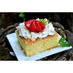 Pastel de Tres Leches (Three Milk Cake) Recipe - A sponge cake is soaked in a mixture of three kinds of milk and topped with whipped cream and optional strawberries.