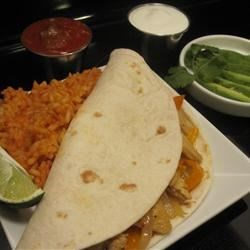 Tangy Chicken Fajitas Recipe - Lime, vinegar and Italian salad dressing mix offer an alternative to the usual Mexican-spiced chicken, onion and green pepper saute.  Serve in the traditional manner, with tortillas and a dollop of sour cream.