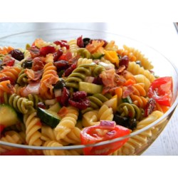 Simple Tasty Pasta Salad Recipe - This pasta salad with cucumber, tomato, and bell pepper is topped with bacon bits and dried cranberries.