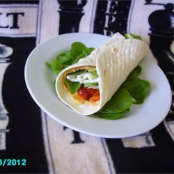Hummus and Artichoke Wrap Recipe - This wrap-style sandwich is packed with hummus, mozzarella cheese, artichoke hearts, roasted red bell pepper, and spinach leaves.