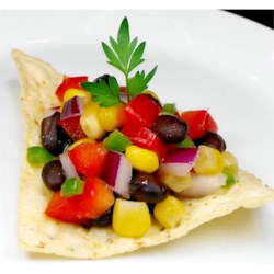 Super Summer Salsa Recipe - This is a different, sweet salsa that is perfect for summer and receives rave reviews! It stars sweet white corn and black beans, with red onion, red pepper, sugar, and the crisp tang of rice wine vinegar. Serve with chips.