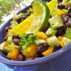 Cucumber, Mango, and Black Bean Salad Recipe - Cucumber, mango, and black beans are tossed together with lime juice and cilantro for a refreshing and crunchy salad.