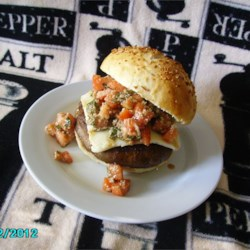 Portobello Mushroom Burger With Bruschetta Topping Recipe - Thick, juicy portobello mushroom caps are grilled and topped with a savory mixture of roma tomatoes, basil, and Parmesan cheese for an Italian-inspired veggie burger.