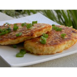 Cheesy Potato Pancakes Recipe - Potato pancakes are flavored with Parmesan and Cheddar cheeses and are sure to please the whole family. Wrap them in foil and bring them along in your lunch.