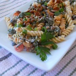 Rae's Italian BS Pasta Salad Recipe - This pasta salad comes together easily and is great for summer get-togethers. Spiral pasta is tossed with Italian dressing, crispy bacon, wilted spinach, and olives for a flavorful side dish.