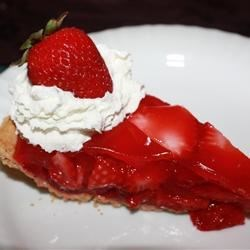 Strawberry Glazed Pie Recipe - This is the quintessential fresh strawberry pie. Lovely sliced berries are coated with a strawberry gelatin glaze, arranged in a graham cracker crust, chilled and piled with mountains of whipped cream.